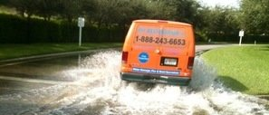 Mold and Water Damage Restoration Van Driving Down Flooded Street
